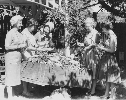 Women shucking corn.