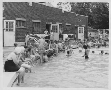 Adult and youth swimmers in and seated around the edge of the Olathe Swimming Pool, 1959