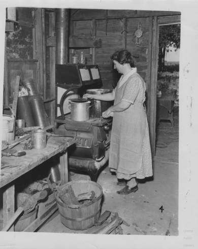 woman cooking at a wood fired stove