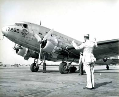 A man in uniform stands before a Naval Air Transport plane, circa 1945