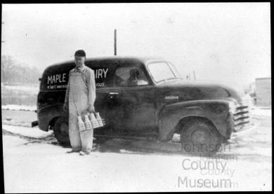 """Horizontal rectangular black and white copy photograph of man identified as Medard """"Boots"""" Vankeirsbilck standing next to delivery truck marked """"MAPLE DAIRY"""" He wears dark colored cap, long sleeved shirt and overalls; holds a wire basket/tray containing 6 bottles of milk.  Snow on ground."""