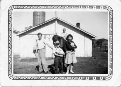 """Black and white photographic print, an informal portrait the four children of Hugh and Mary White on the Wolverine Dairy farm. The four are near a shed on the farm. Three stand while Gene, the youngest, sits on a horse. Bob White stands at the left. Joe stands at the center. He wears a cap and holds a light-colored rabbit. Louise, at the right, wears a dark-colored sweater, light-colored skirt, and holds a dog. The silo is visible in the background at the left. A fence is at the extreme right. Museum label: """"""""2013.22.12"""""""" Handwritten on back of original print: Bob 15 Joe 8 Louise 14 Gene 4 Pony 2"""