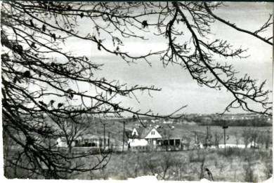 a view of the Charles Ashner dairy farm, the Greenwood Dairy, at 49th Street and Lamar Avenue in Mission. A frame farm house is at the center, surrounded by hillsides. Several outbuildings are partially in view. The bare branches of a tree in the foreground obscure portions of the image at the left and upper two-thirds. Out of focus in the distance are buildings in a nearby residential area.