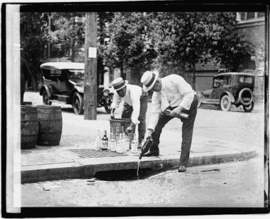 Law enforcement officials emptying alcohol into a storm sewer, probably on the East Coast. Image courtesy Library of Congress.