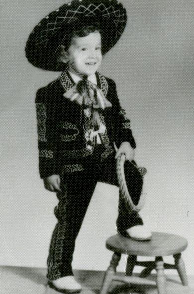 2-A young Jesse Valdez in a mariachi suit that his parents brought back from one of their trips to México. Jesse wore the suit to formal family gatherings. The suit is on display in the Museum's exhibit, Latinos in the Heartland/Latinos en el Corazón de los Estados Unidos.