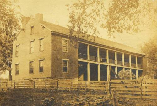Black and white photograph of the exterior of the Shawnee Indian Methodist Mission building. The two-story brick building has a side gabled roof, three visible rectangular chimneys, eleven visible windows, and a built-in porch with wooden classical columns as porch supports. Bricks are missing at the roofline on the side gable and there is some sag visible in the porch. Surrounding the building is a fenced in yard. There are also several trees and shrubs.