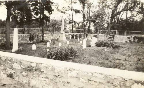 Black and white photograph of the Shawnee Methodist Mission Cemetery. The photograph shows the cemetery where Reverend Thomas Johnson and his family are buried. There is a stone wall surrounding the cemetery with a chain link fence in the background. There are several decorative plants and trees within the cemetery.