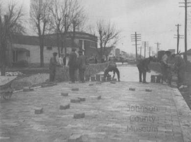 Horizontal rectangular black and white halftone image of workmen laying bricks on Santa Fe Trail Drive in downtown Lenexa. The view is taken looking northeast along the street. Brick roadway in foreground with 7 workmen. Long pile of brick along street at left. Wheelbarrow partially visible at extreme left. Commercial buildings and telephone poles in background. Nearest two-story brick building, to the left of center, was the bank.