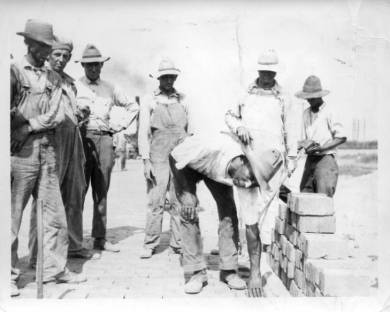 Kansas City-olathe Road: Brick Road That Passed Through Downtown Area Of Lenexa - 6 Brick Workers With Indian Jim, The Noted Bricklayer Of A Numer Of Federal Highways. Black & White photo taken circa 1920s in Lenexa, Kansas.