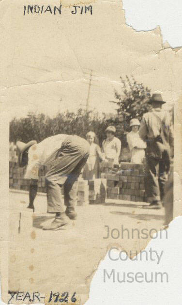 "Vertical rectangular black and white photograph of man, left, bent over facing toward left, laying bricks on roadway. He wears hat, short sleeved shirt, pants with cuffs. Workman at right, back to camera, in hat and overalls. Stacked bricks and three women in background, right. Handwritten in top margin: ""INDIAN JIM."" Handwritten in bottom margin: ""YEAR - 1926."""