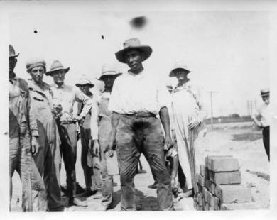 Black and white photo of Indian Jim with 8 other men standing next to a stack of bricks.