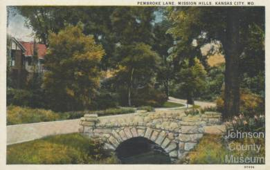 "Color postcard of landscaped area along a street and stone bridge in Mission Hills. The horizontal image has a white border. The view is of a residential area. A portion of a large house is at the extreme left. The street curves near the right of the image. The house is partially obscured by trees. The stone bridge is at the right of the road and is arched over a small waterway. Flowers are in bloom at the right. The postcard was not postally used. The back has a space for the message at the left and the address and stamp at the right. Museum label: ""2005.34.2"" Black text in upper right corner: ""PEMBROKE LANE, MISSION HILLS, KANSAS CITY, MO"" Black text in lower right corner: ""97996"" Vertical text on the back, along left edge: ""PUBLISHED BY R. B. HARNESS GREETING CARD CO., KANSAS CITY, MO."" Vertical text on the back, at the center: ""C. T. AMERICAN ART COLORED"" above loco for ""C T"" ""Chicago"""