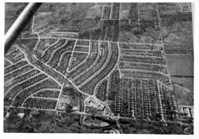 Horizontal rectangular black and white film negative of aerial view of Prairie Village. Area is primarily residential. View looks west. Roe Avenue runs left-right above the center of the image. Mission Road runs left-right along the bottom of the image. Tomahawk Road runs diagonally from the upper left to the bottom edge near the center. 71st Street runs from Mission Road to Roe Avenue to the left of the center of the image. 67th Street runs from Mission Road to the upper right corner of the image. Commercial development on Tomahawk Road near its intersection with Mission Road. Portion of airplane strut visible in top left corner.