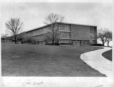 "Horizontal rectangular black and white copy photograph of school exterior on hill, viewed from slightly below. Three story rectangular brick building with large windows. Several bare trees. Sidewalk at right winds uphill to entrance. Handwritten in bottom margin:""SM - East."""