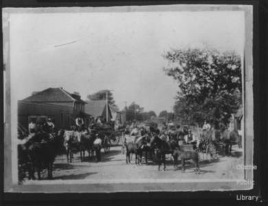 Black and white photo of several people standing with horses and wagons on the street outside a lumberyard.