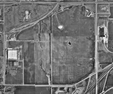 A black and white aerial view of farmland bisected by a few small roads.