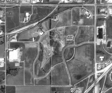 A black and white aerial view of farmland with buildings scattered throughout and roads bisecting the image.