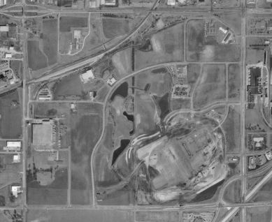A black and white aerial view of farmland with buildings scattered throughout and roads bisecting it.