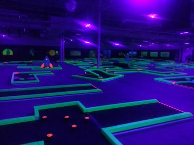 Blacklit minigolf course with space themed decorations.