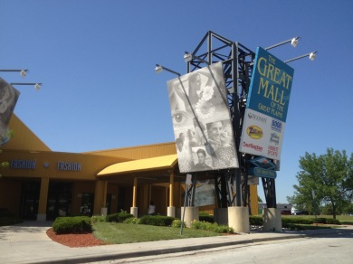 Outside mall entrance. The awning is yellow and billboard signs for the Great Mall stand outside.