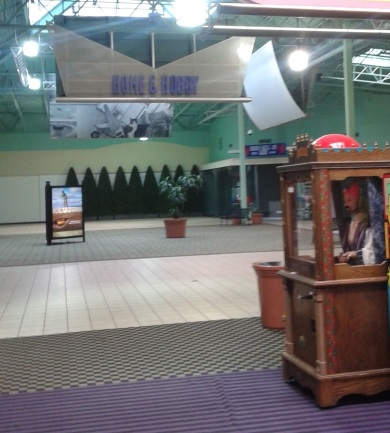 An automated fortune teller booth stands in the middle of a mall hallway in front of the Home and Hobby store.