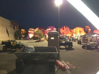 A night shot behind the Great Mall. In the foreground are dumpsters and portapotties, and on the horizon are several lit hot air balloons.