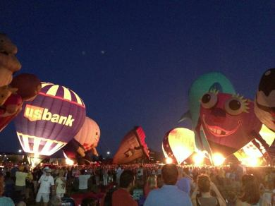 A crowd of people with lit hot air balloons floating above them.