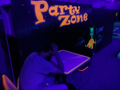 A blacklit picture of a teenage boy sitting at a table with the words Party Zone lit above his head. a glowing green alien stands opposite him.